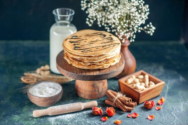 Vooraanzicht heerlijke pannenkoeken met melk en noten op donkerblauwe melk dessert ontbijt honing zoete ochtend taart taart