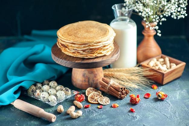 Vooraanzicht heerlijke pannenkoeken met melk op donker ontbijt honing cake taart ochtend thee dessert melk zoet