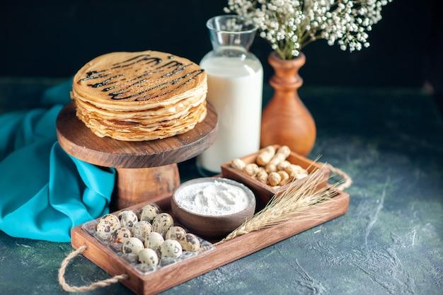 Vooraanzicht heerlijke pannenkoeken met noten op de donkerblauwe ochtendtaart dessert zoete cake honing ontbijt melk