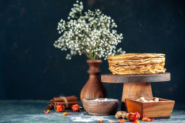 Vooraanzicht heerlijke pannenkoeken met noten op donkerblauwe melk dessert ontbijt ochtend taart cake honing