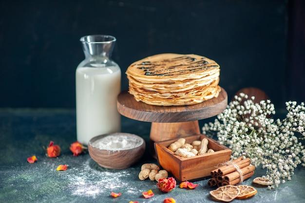 Vooraanzicht heerlijke pannenkoeken met noten op donkerblauwe melk dessert zoete ochtendtaart honing ontbijt