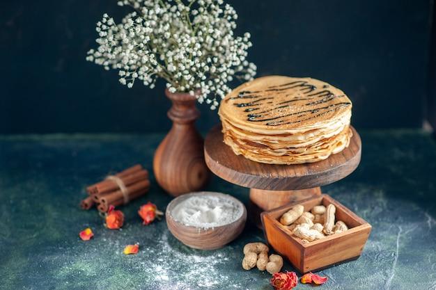 Vooraanzicht heerlijke pannenkoeken met noten op een donkerblauwe melk dessert ontbijt zoete ochtend taart cake honing