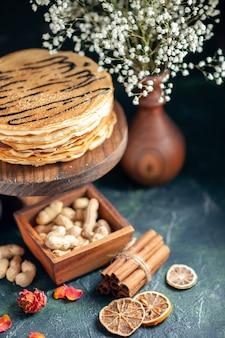 Vooraanzicht heerlijke pannenkoeken met noten op het donkerblauwe melkdessert zoete ochtendtaart cake honing ontbijt