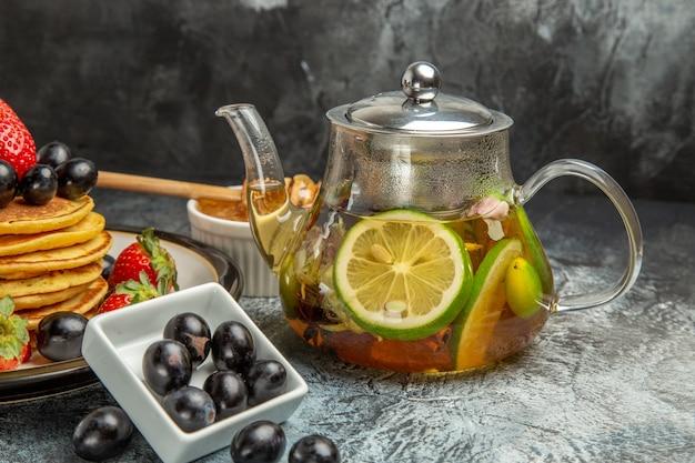 Vooraanzicht heerlijke pannenkoeken met olijven en waterkoker met thee op licht fruit voedsel