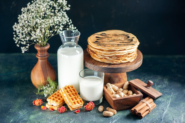 Vooraanzicht heerlijke pannenkoeken met verse melk en noten op donkerblauwe dessert taart honing cake ontbijt zoete melk ochtend