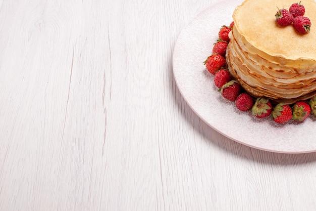 Vooraanzicht heerlijke pannenkoeken met verse rode aardbeien op witruimte