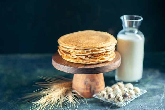 Vooraanzicht heerlijke pannenkoeken op houten bureau en donker ontbijt dessert taart taart zoete melk honing ochtend