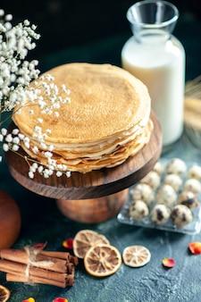 Vooraanzicht heerlijke pannenkoeken op houten bureau en donkere ontbijttaart, zoete honingthee dessertmelk