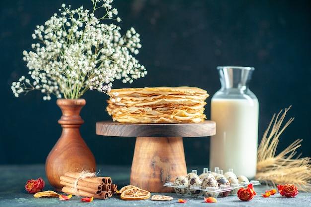 Vooraanzicht heerlijke pannenkoeken op houten bureau en donkere ontbijttaart, zoete melk, honing ochtendthee