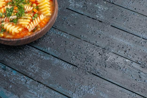 Vooraanzicht heerlijke pastasoep van spiraalvormige italiaanse pasta met greens op donkere achtergrond schotel italiaanse pastasaus soep diner