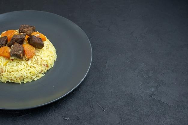 Vooraanzicht heerlijke pilaf gekookte rijst met gedroogde abrikozen en vleesplakken binnen plaat op donkere ondergrond