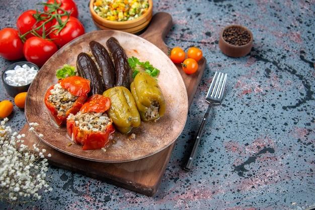 Vooraanzicht heerlijke plantaardige dolma met salade en tomaten op blauwe achtergrond
