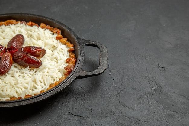 Vooraanzicht heerlijke plov gekookte rijstmaaltijd met rozijnen in pan op donkere oppervlakte eten rijst oostelijke dinermaaltijd dinner