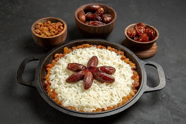 Vooraanzicht heerlijke plov gekookte rijstmaaltijd met rozijnen op het donkere oppervlak eten rijst oosterse dinermaaltijd