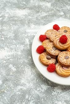 Vooraanzicht heerlijke ronde koekjes met frambozenconfituren op witte ruimte