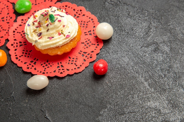 Vooraanzicht heerlijke roomcake dessert voor thee met snoepjes op grijze achtergrond cake cream biscuit zoete koekjesdessert