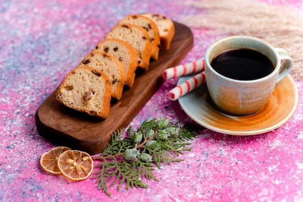 Vooraanzicht heerlijke rozijnencake gesneden taart op roze oppervlak bakken taart suiker zoete koekkoekjes