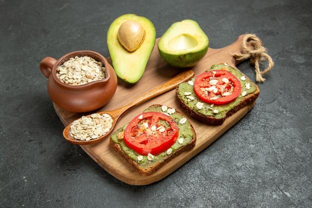 Vooraanzicht heerlijke sandwiches met avocado en rode tomaten op grijze achtergrond lunch snack hamburger sandwich maaltijd