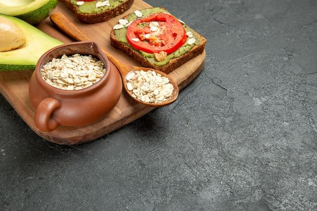 Vooraanzicht heerlijke sandwiches met avocado en rode tomaten op grijze achtergrond lunch snack maaltijd hamburgersandwich