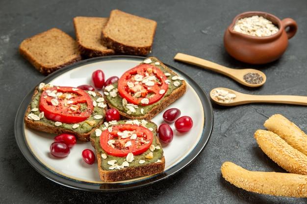 Vooraanzicht heerlijke sandwiches met avocado pasta en tomaten in plaat op grijs bureau snack broodje hamburger sandwich brood