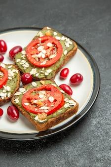 Vooraanzicht heerlijke sandwiches met avocado pasta en tomaten in plaat op grijze achtergrond hamburgers sandwich broodje snack brood