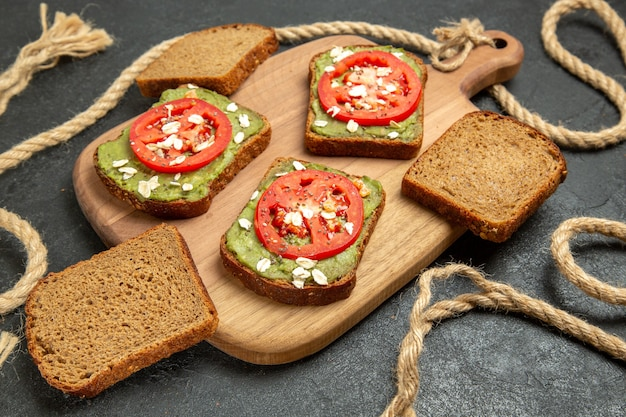 Vooraanzicht heerlijke sandwiches met wassabi en rode tomaten op de grijze achtergrond brood hamburger sandwich maaltijd snack