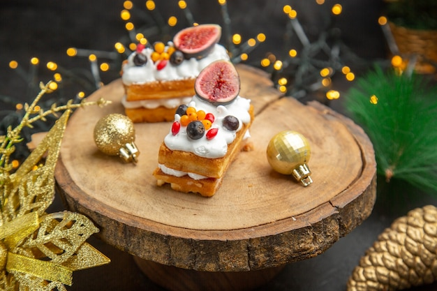 Vooraanzicht heerlijke slagroomtaarten rond nieuwjaarsboomspeelgoed op donkere achtergrondcake, zoet fotoroomdessert