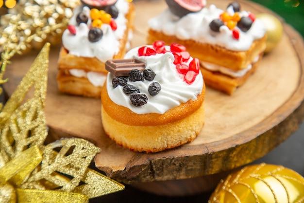Vooraanzicht heerlijke slagroomtaarten rond nieuwjaarsboomspeelgoed op een donkere achtergrond dessertcake zoete fotoroom