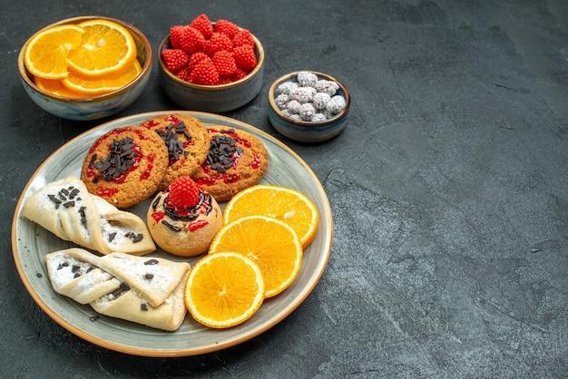 Vooraanzicht heerlijke suikerkoekjes met gebak en sinaasappelschijfjes op donkere suikerkoekjes, zoete cakekoekjesthee