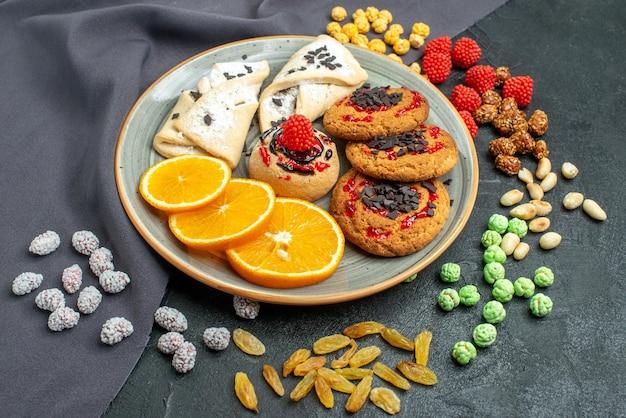 Vooraanzicht heerlijke suikerkoekjes met gebak en sinaasappelschijfjes op donkere suikerkoekjes, zoete koekjestheecake