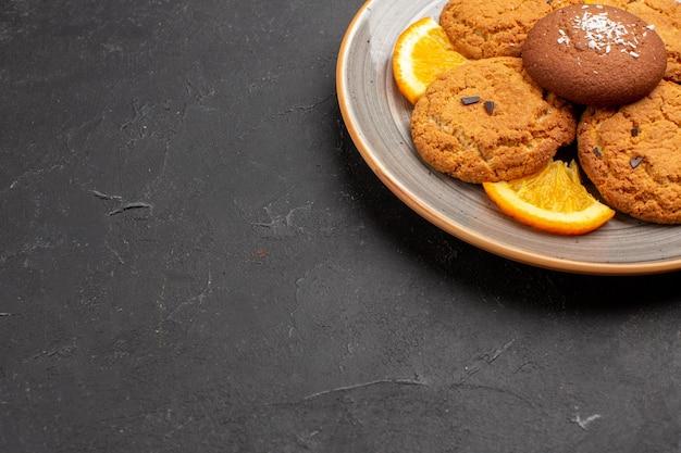 Vooraanzicht heerlijke suikerkoekjes met gesneden sinaasappels in plaat op donkere achtergrond suikerkoekjes zoete koekjes fruit