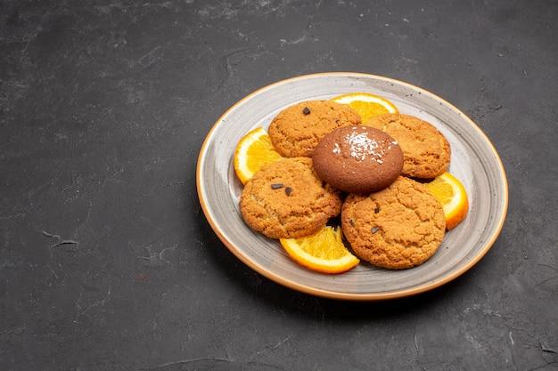 Vooraanzicht heerlijke suikerkoekjes met gesneden sinaasappels in plaat op donkere bureausuikerkoekjes zoet koekjesfruit