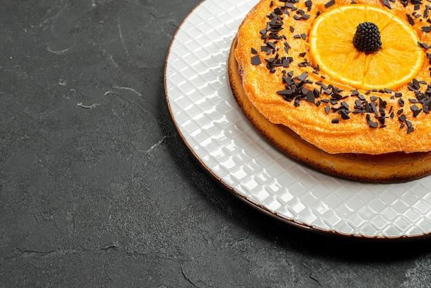 Vooraanzicht heerlijke taart met chocoladeschilfers en stukjes sinaasappel op donkere achtergrond dessert thee taart taart fruit biscuit