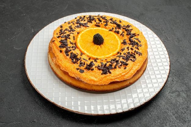 Vooraanzicht heerlijke taart met chocoladeschilfers en stukjes sinaasappel op donkere achtergrond theetaart dessert cake fruitkoekje