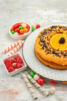 Vooraanzicht heerlijke taart met kleurrijke snoepjes op witte achtergrond taart biscuit zoete dessert regenboog dessert