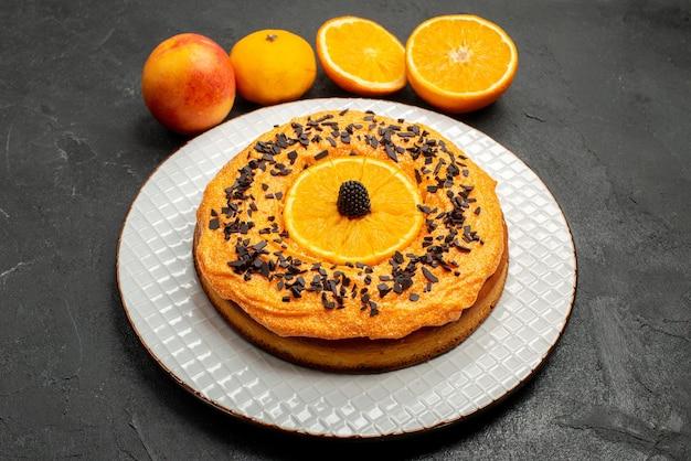 Vooraanzicht heerlijke taart met stukjes sinaasappel op donkere achtergrond fruit dessert taart cake biscuit thee