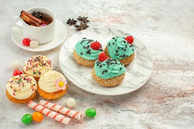Vooraanzicht heerlijke taarten met snoep en kopje thee op witte achtergrond thee snoep biscuit taart zoet dessert