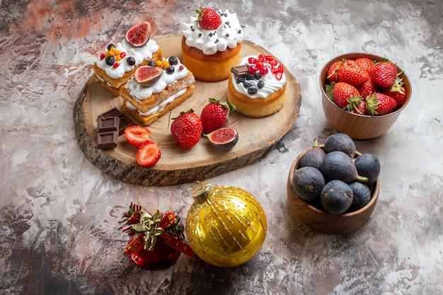 Vooraanzicht heerlijke taarten met vers fruit op lichte achtergrond kerst cake dessert biscuit kleur