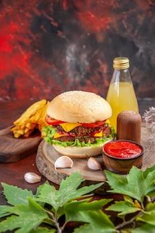 Vooraanzicht heerlijke vlees hamburger met frietjes op donkere achtergrond