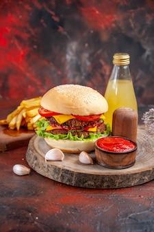 Vooraanzicht heerlijke vlees hamburger met frietjes op donkere vloer