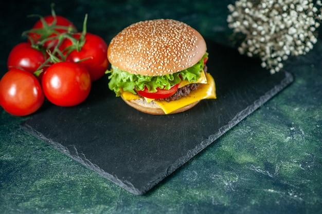 Vooraanzicht heerlijke vlees hamburger met groene salade kaas en tomaten op donkere achtergrond
