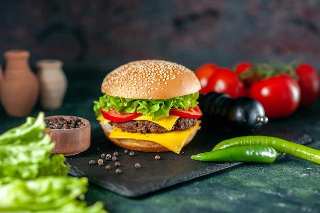Vooraanzicht heerlijke vlees hamburger met rode tomaten op donkere achtergrond
