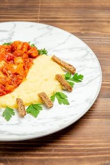 Vooraanzicht heerlijke vleesplakken met aardappelpuree en groenten op houten bureau vleesbroodmaaltijd aardappelvoedselschotel