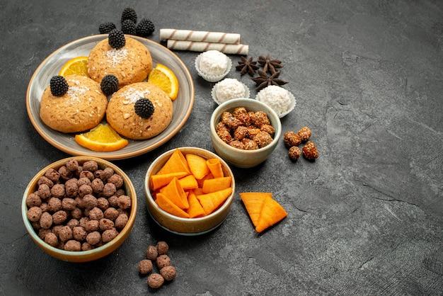 Vooraanzicht heerlijke zandkoekjes met chips en stukjes sinaasappel op een donkere achtergrond, zoet fruitcockiekoekje