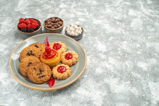 Vooraanzicht heerlijke zandkoekjes met koekjes en snoepjes op witruimte