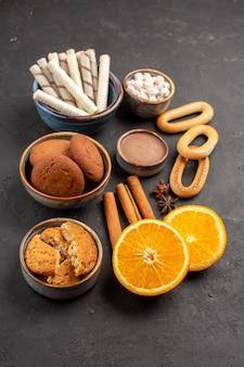 Vooraanzicht heerlijke zandkoekjes met vers gesneden sinaasappelen op donkere achtergrondkoekjes, zoete citrussuikerkoekjesfruit