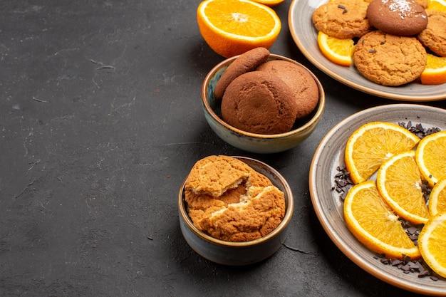 Vooraanzicht heerlijke zandkoekjes met vers gesneden sinaasappelen op een donkere achtergrond, suikerkoekje, zoete koekjes, fruitcake