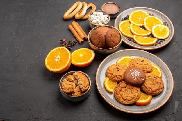 Vooraanzicht heerlijke zandkoekjes met verse sinaasappelen op donkere achtergrondkoekjes suiker fruitkoekje zoete citrus sweet