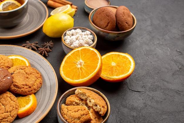 Vooraanzicht heerlijke zandkoekjes met verse sinaasappels en kopje thee op een donkere achtergrond, fruitkoekje, zoete koekje citrus