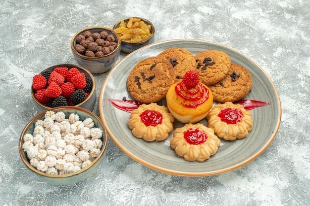 Vooraanzicht heerlijke zandkoekjes met zoete koekjes en snoepjes op witruimte